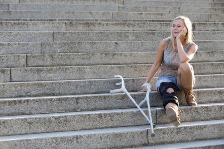 blonde vrouw met krukken zittend op de trap Stockfoto