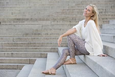 blonde vrouw, zittend op trappen en glimlacht