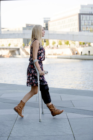 immobility: blonde woman in a dress walking with crutches Stock Photo