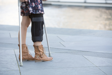 close up of woman in a dress walking with crutches Stock Photo