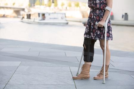 松葉杖で歩くドレスを着た女性のクローズ アップ