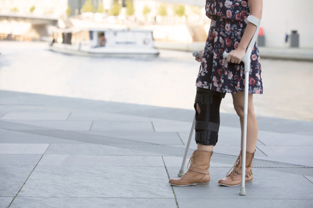 broken knee: close up of woman in a dress walking with crutches Stock Photo