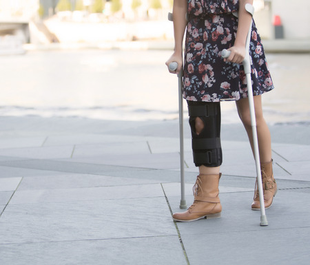 close up of woman in a dress walking with crutches photo