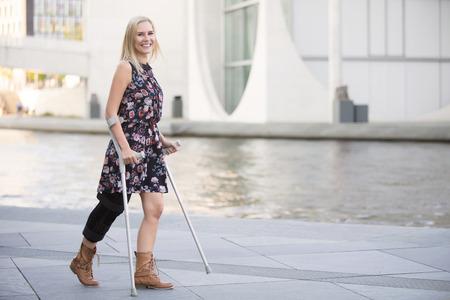 blonde vrouw in een jurk lopen met krukken