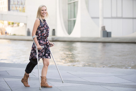 blonde woman in a dress walking with crutches Reklamní fotografie