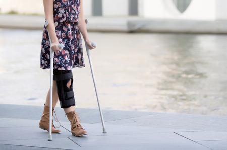 close up van de vrouw in een jurk lopen met krukken