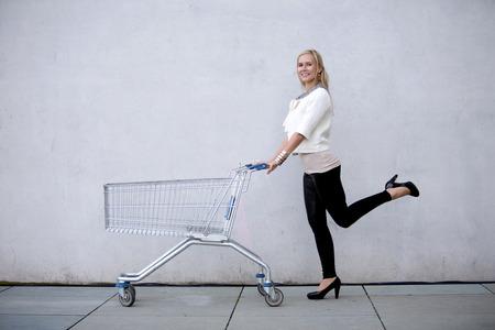 shoppingcart: blonde woman is pushing a shoppingcart