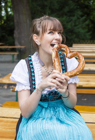 young woman in dirndl in beer garden with a pretzel photo