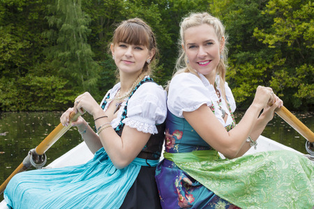 tracht: two woman with dirndl in a rowing boat Stock Photo