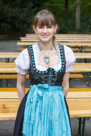 a young woman in dirndl in beer garden photo