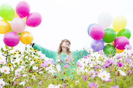 young woman with ballons on a field of flowers photo