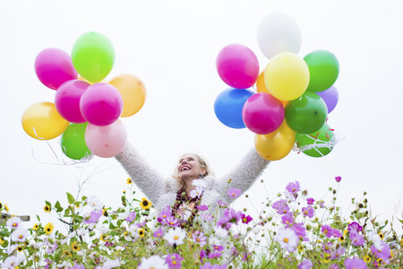 blonde woman with balloons on a field of flowers photo