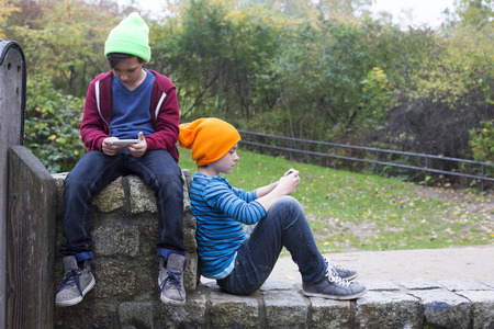 two young boys sitting outside and playing with their phones photo