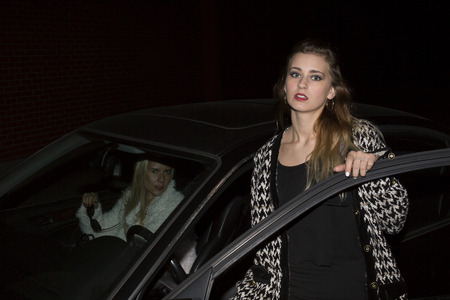 two women getting out of their car in the night photo