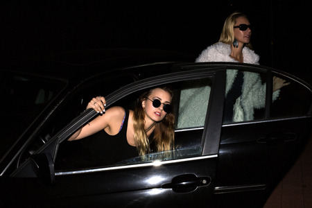 two women with sunglasses getting out of their car in the night photo