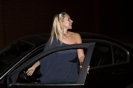 blond woman getting out of her car in the night photo