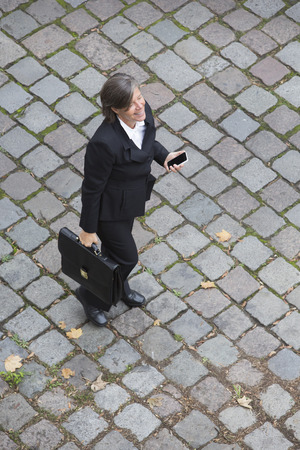 birdseye view: birds-eye view of a businesswoman walking on the streets with a phone in her hands