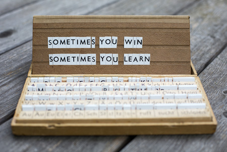 """de woorden """"Soms win je soms moet je leren"""" op een oude school brievenbus"""
