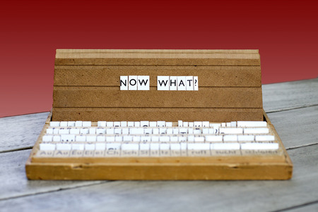 what if: the word now what? on an old school letter box on a red background Stock Photo