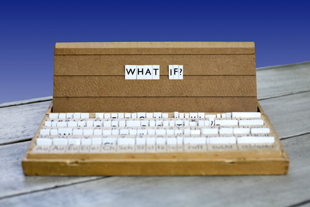 what if: the word what if? on an old school letter box on a blue background