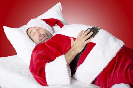hombre rojo: hombre vestido como Pap� Noel que duerme en la cama y tiene es grande est�mago