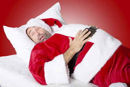 isolated man: man dressed as Santa Claus sleeping in bed and holds is big stomach