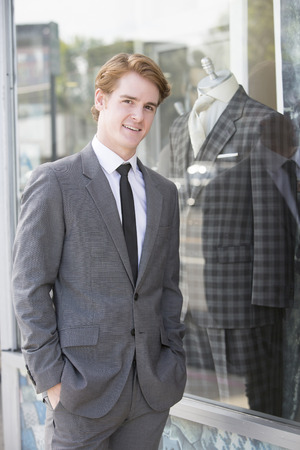 departmentstore: man in suit standing at a clothing storefornt