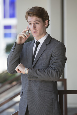 businessman standing outside talking on the phone