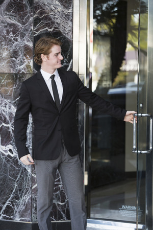 スーツを着た男が開きドアと笑顔 写真素材