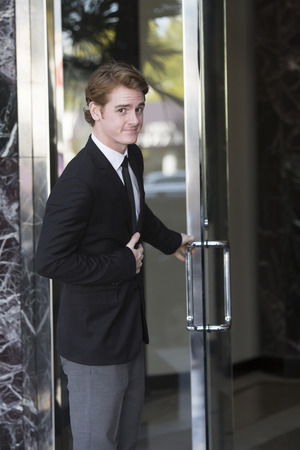 man in suit opens a door and smiles Stock fotó