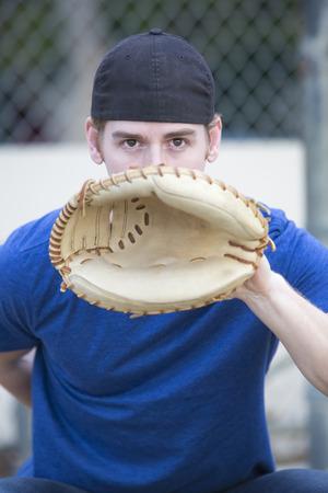 guante de beisbol: hombre joven con guante de b�isbol en un campo de deportes