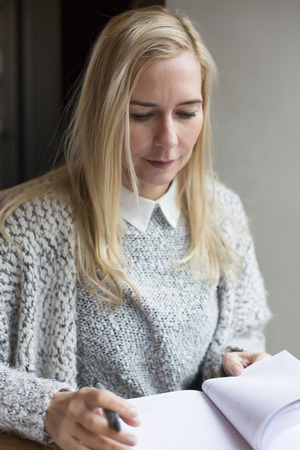 blond woman writing in a book photo