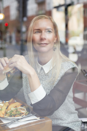 food woman: blond woman eating a burger and looking through window