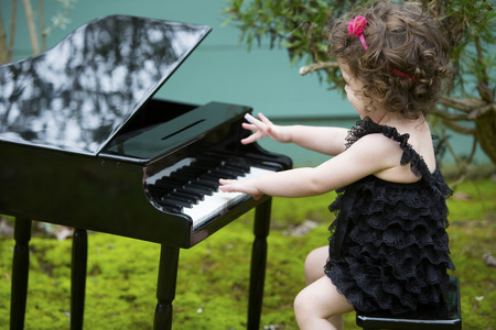 little girl playing on a toy piano photo