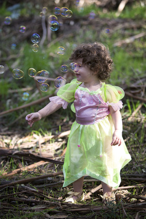 enchanting: little girl in forest dressed as a fairy with soap bubbles