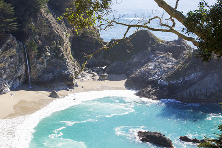 mcway: beautiful McWay falls in Big Sur California with sandy beach and blue water