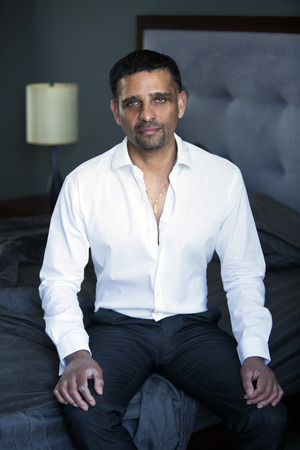 pakistani ethnicity: handsome businessman in a white shirt sitting in bedroom