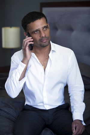 pakistani ethnicity: handsome businessman on the phone sitting in bedroom