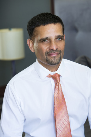 pakistani ethnicity: handsome businessman in shirt and tie sitting in bedroom