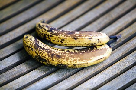 twee overrijpe bananen op hout