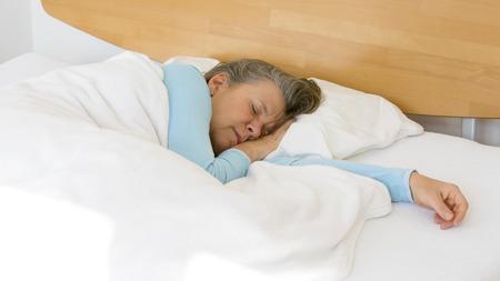 oudere vrouw in bed liggen en slapen rustig Stockfoto
