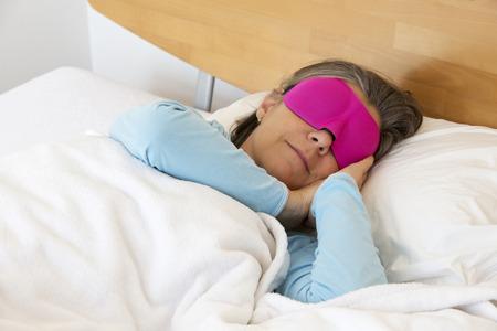sleep mask: older woman lying in bed and sleeping peacefully with a sleep mask on Stock Photo