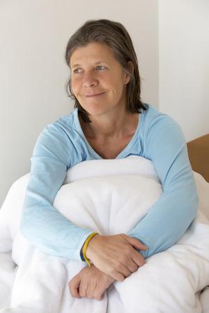 oudere vrouw zitten in bed en op zoek gelukkig