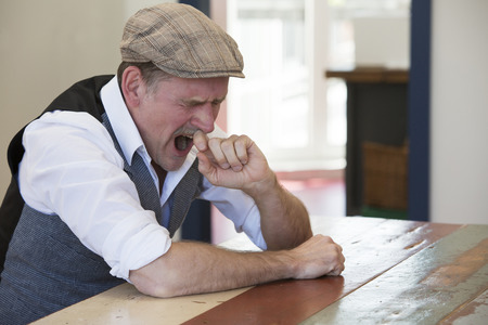 50s: man in his 50s sitting at table and is yawning