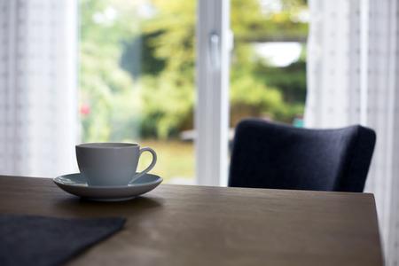 庭園を眺められるリビング ルームのテーブルの上の白いカップ