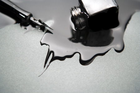 old fashioned pen with a glass of spilled black ink