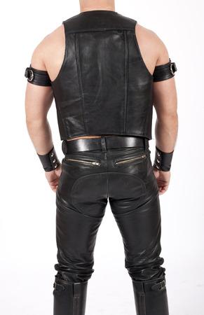 backside of a leathermen dressed in black fetish gear photo