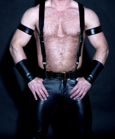 hairy male: hairy muscular male torso dressed in fetish black leather Stock Photo