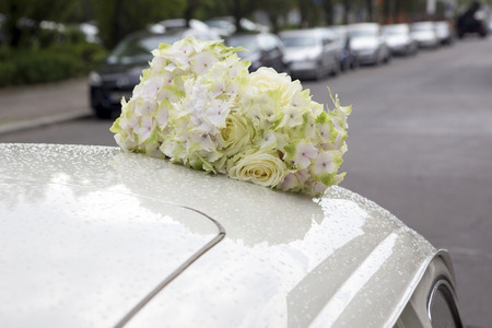 bouquet of white flowers on the roof of a car photo