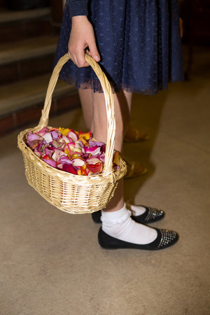 flowergirl: closeup of a flower girl holding a basket full of petals
